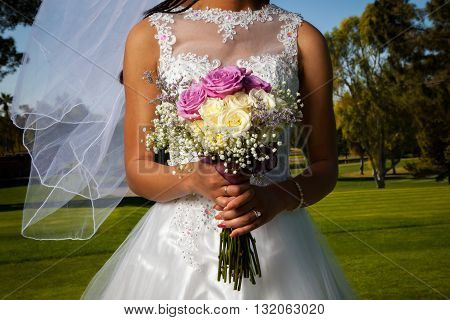 Detail image of an African American bride holding her rose bouquet in front of her. Her veil blows gently in the wind.