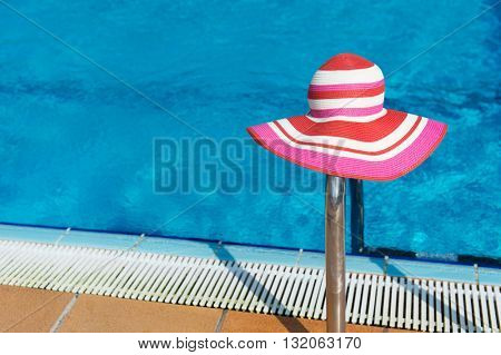 Luxury swimming pool with pink female sun hat