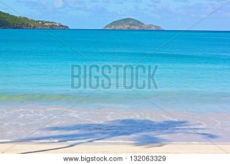 St Thomas Island Megans Bay beach early in the morning. Azure beach with white sand and palm shadow.