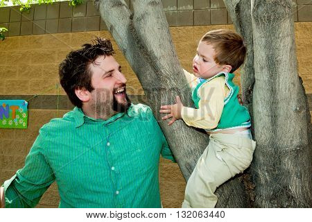 A young dad smiles and laughs at his young son who is not sure he is happy about being in a tree. They are well dressed for Easter Sunday.