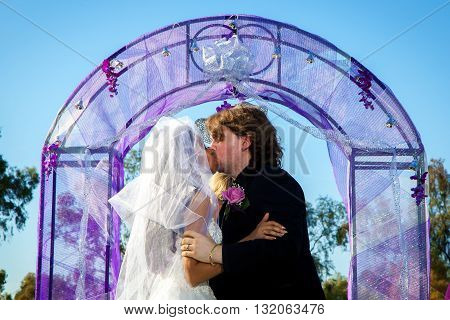 A couple shares their first kiss at the alter during their wedding ceremony.