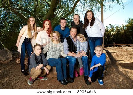 Portrait of a large family under a mesquite tree. They are close and connected.