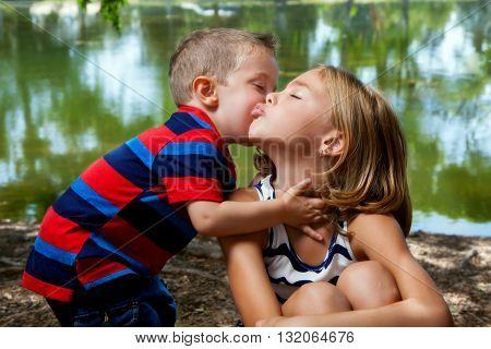 A little brother leans in to kiss his big sister on the cheek as she puckers her lips to the side of his face.