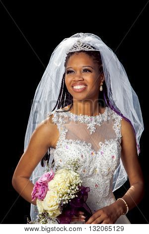 Portrait of a beautiful African American bride on her wedding day. Black background with a back lit veil. She looks off to the distance with a stunning smile and lovely boquet of roses.