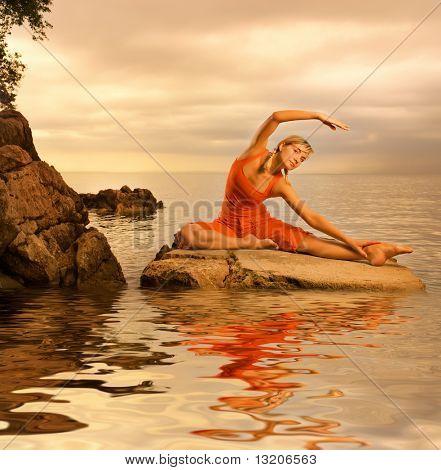 Красивая молодая женщина делает йога упражнения на открытом воздухе