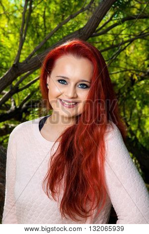 A beautiful teenaged girl with dyed red hair poses for a portrait in front of trees. She has a tilted head lovely smile and bright blue eyes.