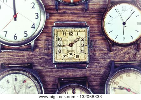 A selection of retro and antique watches over old wood background. Filtered to look like an aged instant photo.