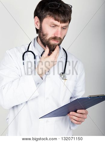 close-up portret of a Doctor holding a map-case for note, stethoscope around his neck. He rubs his chin. different emotions.