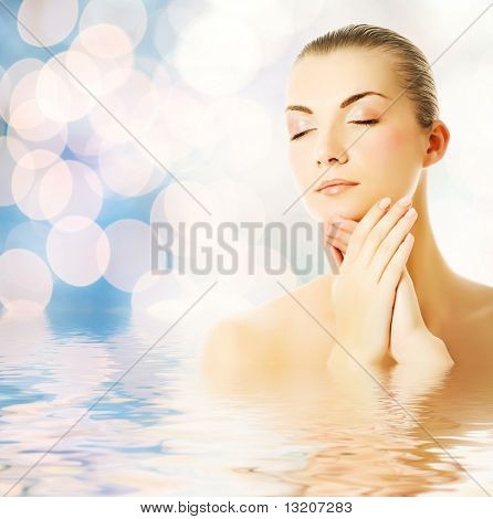 Beautiful young woman in water massaging her face