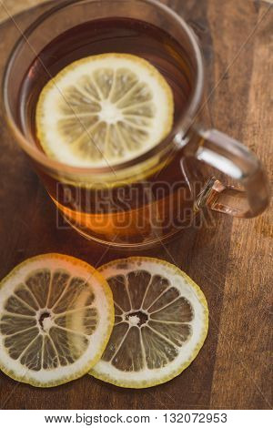 Top view of black tea with lemon in cup and on wooden plank table.