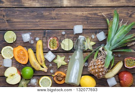 Tropical fruits with ice and a bottle of refreshing soda on wooden background
