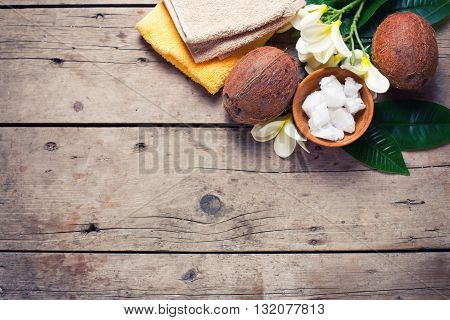 Coconut spa. Coconuts coconut oil and towels on vintage wooden background. Selective focus. Natural organic spa products. Place for text. Flat lay.