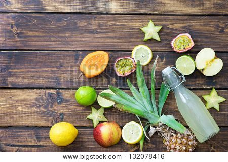 Tropical fruits and bottle of soda on wooden background