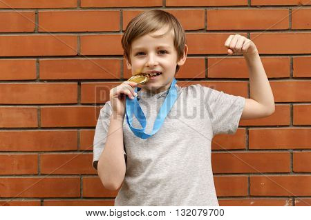 blond boy is happy gold medal - champion, winner