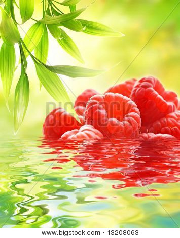 Ripe raspberries reflected in water
