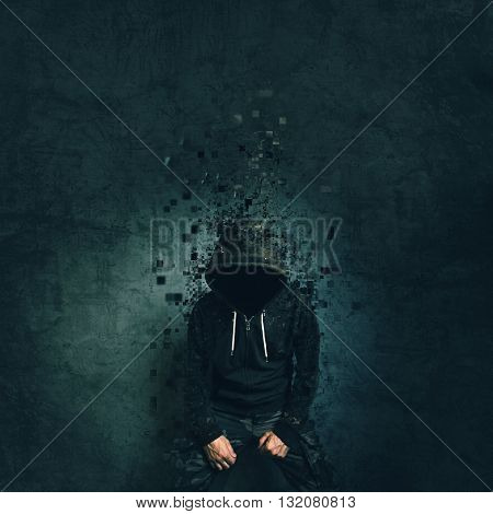 Spooky evil criminal person with hooded jacket dissolving in front of concrete wall.