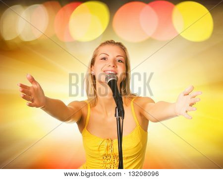 Beautiful young singer on abstract background