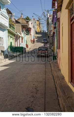 Santiago de Cuba Cuba - January 10 2016: Typical scene of one of streets in the center of Santiago de cuba - Colorful architecture people walking around. Santiago is the 2nd largest city in Cuba