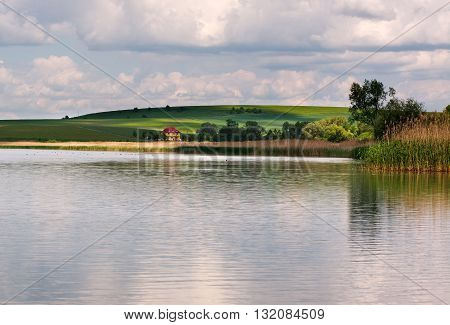 Peaceful lake landscape in the village under the blue sky