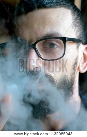 Bearded Man Smoking Vaporizer And Blows Smoke