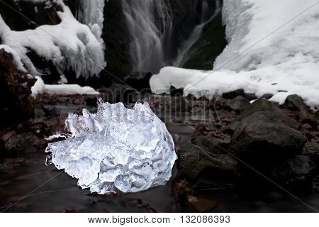 Spiky Piece Of Icrystal Ce With Abstract Cracks Inside. Fallen Icicle Bellow Waterfall,