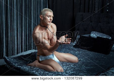 Metrosexual man playing on the bed in his neck dog collar.