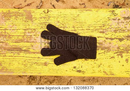 Lost Woolen Gloves On Yellow Bench. Sandy Gren Wooden Bench.  Sandbox With Dirty Sand In Kindergarde