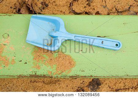 Blue Children Shovel Toy On White Sand, Plastic Play For Game. Mound Of Sand In Kindergarden.