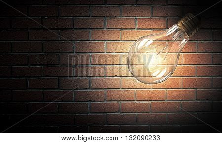 Light bulb on brick surface