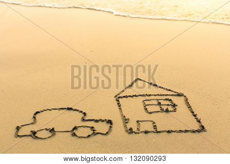 Car and the house drawn on the sand of a beach with the soft wave.