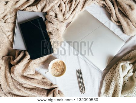 A cup of coffee diary and address book with the laptop on the bed with a beige plaid
