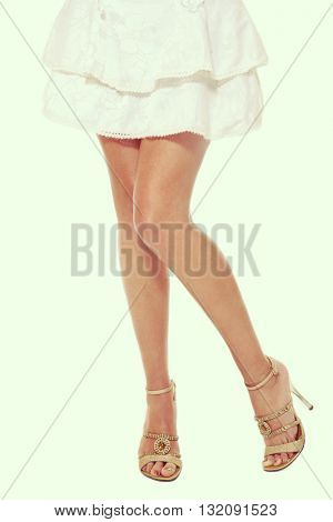 Vintage style shot of legs of slim tanned sexy woman in sparkly stilettos and white skirt