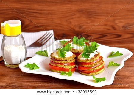Delicious appetizer of fried zucchini, fresh tomatoes, yoghurt and parsley. Vegan zucchini recipe. Vegetarian snack with squash and tomatoes. Summer vegetable dish. Napkin, fork, salt shaker