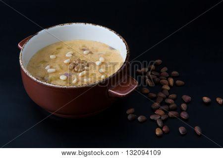 Sweet oatmeal porridge with pine nuts on black