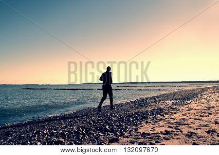 Tall Man In Dark Sportswer Running And Exercising On Stony Beach At Breakwater.