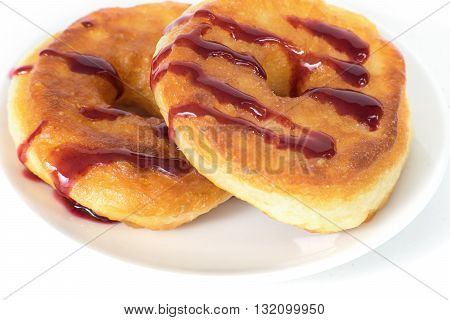 Unhealthy fat donuts with a berry jam in a white plate isolated on white