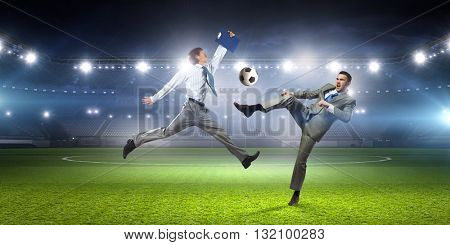 Two businessmen fight for ball