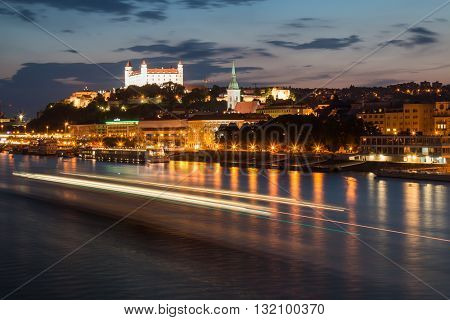 Bratislava, Slovakia - May 29, 2016 City Bratislava capital of Slovak Republic. Night view on the river Danube with a passing boat cathedral in the old city and the castle.
