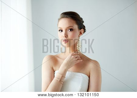 beauty, jewelry, wedding accessories, people and luxury concept - beautiful asian woman in white dress or bride with golden earrings and bracelet