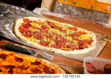 Fresh original Italian raw pizza on a shovel.