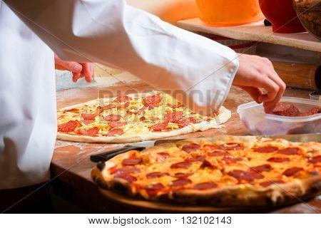 Fresh original Italian pizza, preparation in traditional style.
