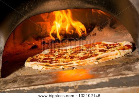 Fresh original Italian pizza in a traditional wood-fired stone oven. poster