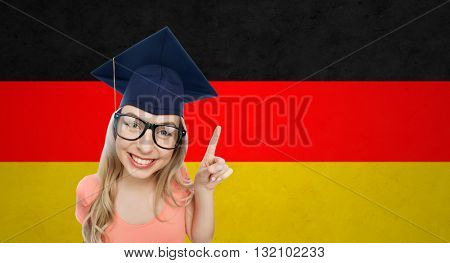 people, graduation and national education concept - smiling young student woman in mortarboard and eyeglasses pointing finger up over german flag background