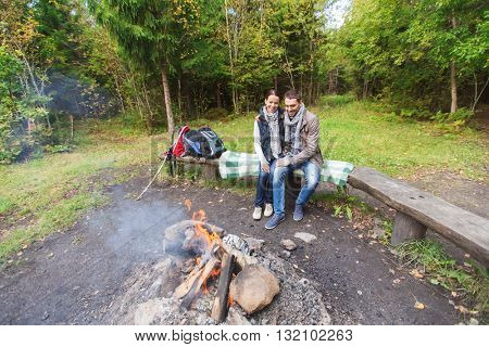 camping, travel, tourism, hike and people concept - happy couple sitting on bench and hugging near campfire at camp in woods