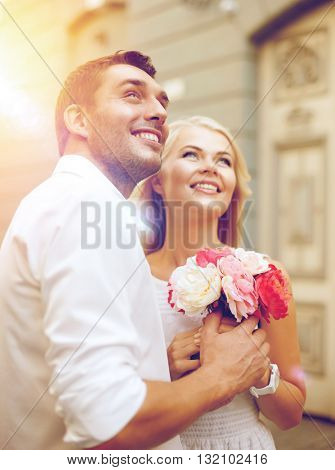 summer holidays and dating concept - couple with bouquet of flowers in the city