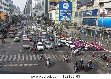 BANGKOK THAILAND - APR 29 : people walk across crosswalk in traffic at Asoke junction on april 29 2016 thailand. traffic jam is one of worse issue of Bangkok