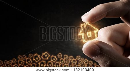House sign between fingers