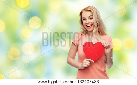 love, romance, charity, valentines day and people concept - smiling young woman or teenage girl with blank red heart shape over summer green lights background