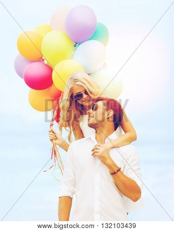 summer holidays, celebration and dating concept - couple in sunglases with colorful balloons over blue sky background