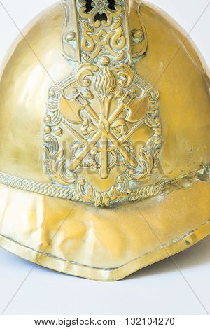 British Other Ranks Merryweather Brass Fire Helmet used during the blitz Second World War with consequent damage. Close up of badge showing crossed axestorch and hose pipes